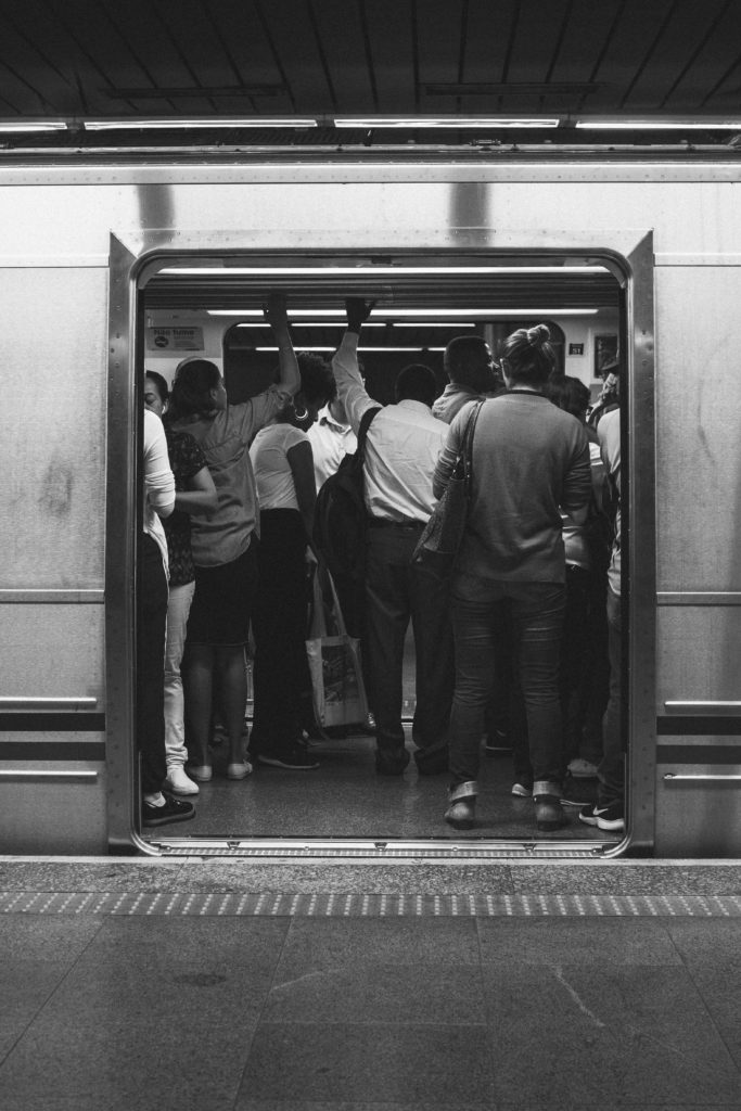 Open subway doors showing a semi crowded train full of men and women.