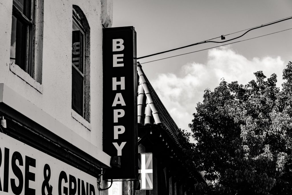 """Sign on side of building that reads """"be happy"""" tree and sky in the background"""