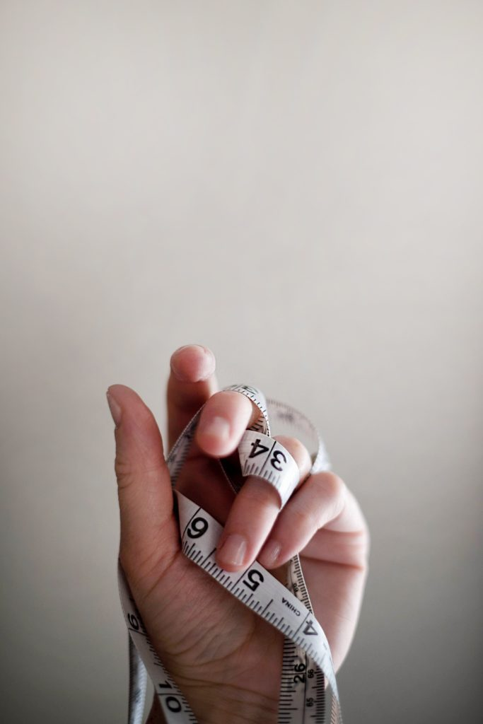 Hand holding measuring tape to track weight loss from taking protein powder.