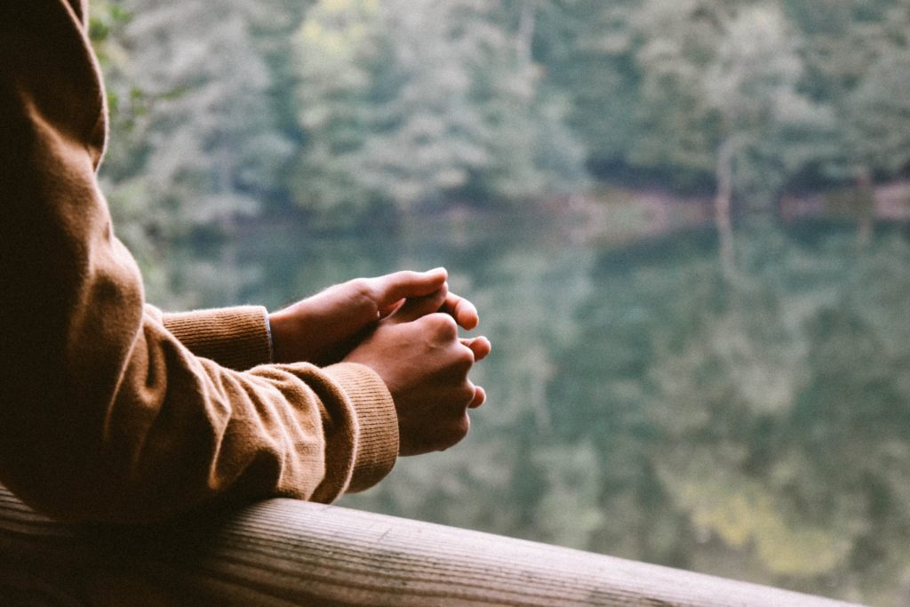 Man's hands crossed overlooking a lake surrounded by trees.