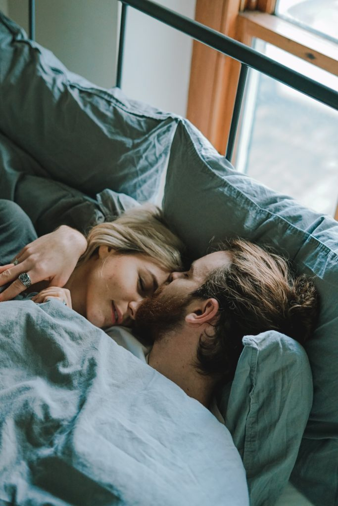 Man and woman laying in bed together talking about their sex life.